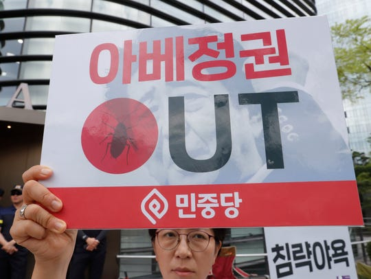 """Japan's Cabinet on Friday approved the removal of South Korea from a """"whitelist"""" of countries with preferential trade status, a move sure to fuel antagonism already at a boiling point over recent export controls and the issue of compensation for wartime Korean laborers. The signs read: """"The government of Japanese Prime Minister Shinzo Abe."""""""