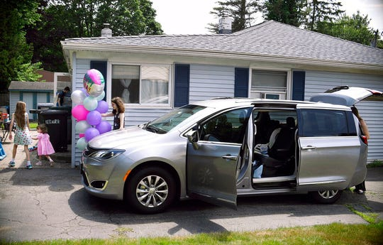 """In this Tuesday, July 16, 2019, Melanie Matcheson, right, unloads her Chrysler Pacifica as her son Alexander and daughters Keiley, Caroline, and Georgianna head back into the house in Cheshire, Conn. Melanie Matcheson doesn't care that a minivan could have the stigma of a 1990s soccer mom. """"I think the newer ones look very nice,"""" she said."""