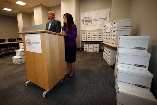 Rose Pugliese, Mesa County, Colo., commissioner, right, and Don Wilson, mayor of Monument, Colo., speak during a news conference Thursday in Denver to announce that their campaign has turned in thousands of voter signatures in hopes of repealing a new law that would pledge the state's presidential electoral votes to the winner of the national popular vote.