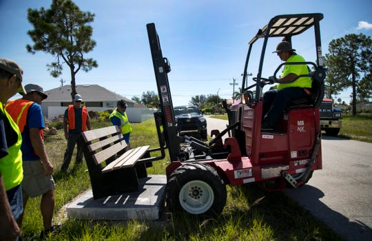 Ray Kijak of ABC Supply Company moves a bench onto a concrete slab at one of Cape Coral's bus stops on Saturday, July 27, 2019.