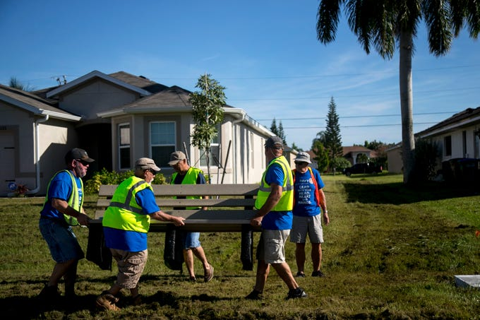 A group of volunteers from the Rotary Club of Cape Coral carry one of the 200 benches that were installed at bus stops in Cape Coral.