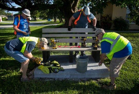 Cape Coral Rotary Club members John Calla, left front, Murray Smith, left rear, Jim Geudtner and Lou Peppe, right, install a bench at a bus stop in southwest Cape Coral on Saturday, July 27, 2019.