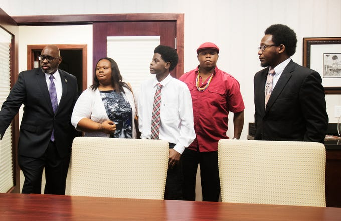 Lavaris Johnson, 14, center,  is flanked by from left, attorney Cedric Hall, his mother Olivia Johnson, his uncle Corey Hampton and community activist Earl Sparrow Jr. before a press conference at attorney Joe North's Fort Myers offices on Friday August, 2, 2019. The Lee County Sheriff's Office arrested Johnson for skipping out on paying fare for a taxi ride from Cape Coral to Lehigh. His mother says he is being wrongly accused and has video survellance footage to prove it.