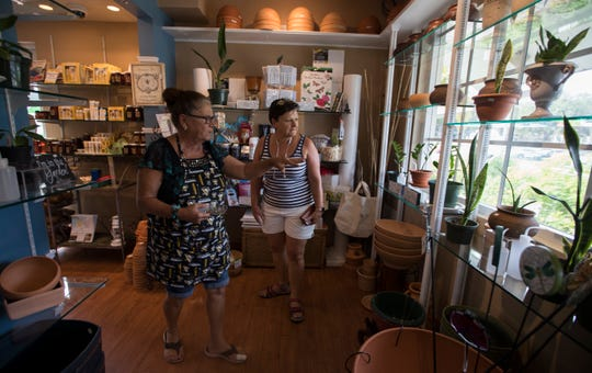 Susan Corcoran, an employee at Thrifty Garden in Fort Myers, speaks with Fort Myers resident Lise McStravock during her first visit to the location. The business, which opened in January of 2018, carries plants, garden supplies, books, gifts, and locally made items.