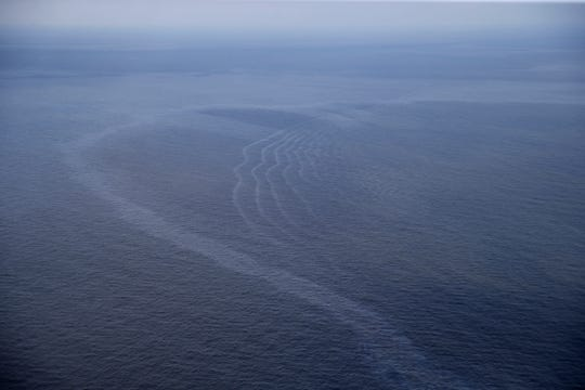 FILE - This March 31, 2015, aerial file photo, shows an oil sheen drifting from the site of the former Taylor Energy oil rig in the Gulf of Mexico, off the coast of Louisiana. A new federally led estimate of oil seeping from a platform toppled off Louisiana 14½ years ago is below other recent estimates. But the report contradicts the well owner's assertions about the amount and source of oil. Oil and gas have been leaking into the Gulf of Mexico since a subsea mudslide caused by Hurricane Ivan on Sept. 15, 2004 knocked over a Taylor Energy Co. production platform.