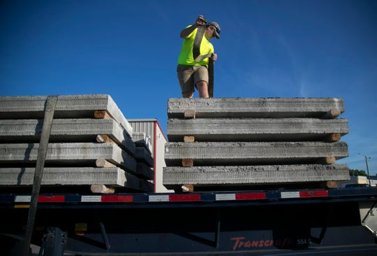 Chase Mason secures concrete slabs for benches that are being put at bus stops in Cape Coral on Saturday, July 27, 2019. ABC Supply Company volunteers stored the donated slabs then delivered them to each of the bus stop locations.