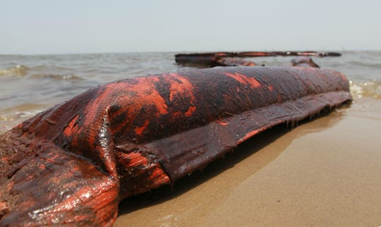 An oil coated containment boom is seen on the beach after it was moved out of place during high winds and waves in the past days which brought oil ashore from the Deepwater Horizon oil spill in the Gulf of Mexico July 9, 2010 in Waveland, Mississippi. FILE