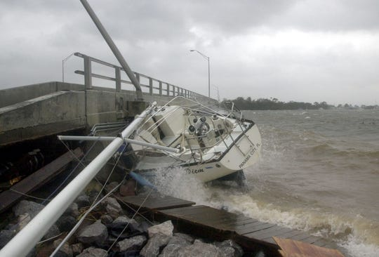 FILE - In this Sept. 16, 2004 file photo, waves crash against a sailboat lodged under a bridge in Fort Walton Beach, Fla., after Hurricane Ivan struck the gulf coast. Federal regulators believe a persistent oil spill in the Gulf of Mexico that began after a drilling platform was toppled during Hurricane Ivan in 2004 will continue for 100 years or more if left unchecked, according to estimates obtained by The Associated Press that provide new  details about the extent of the problem.