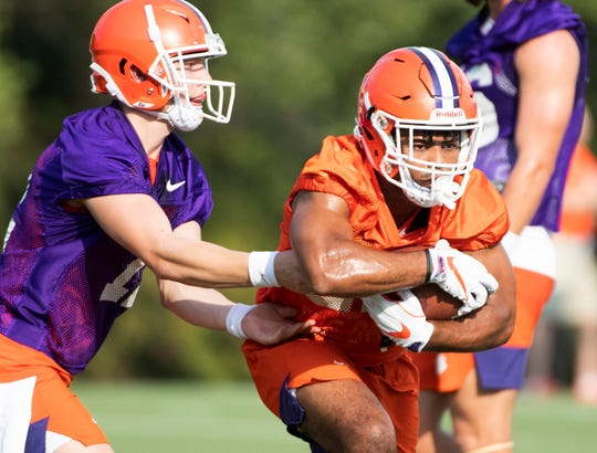 Clemson quarterback Ben Batson (12) passes the ball to running back Darien Rencher (21) during practice at the Allen N. Reeves Football Complex August 2, 2019.