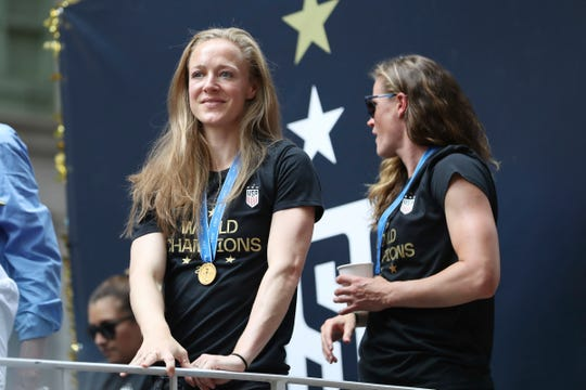 United States defender Becky Sauerbrunn, left, looks at the crowd on a float while being honored with a ticker tape parade along the Canyon of Heroes on July 10 in New York.