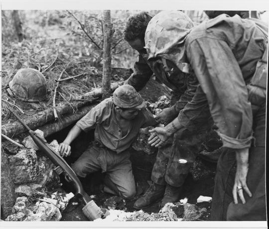 Marines coax a Japanese Navy man into surrendering on Guam in July 1944. In August 1944, a group of CHamorus were armed and trained to patrol the island and hunt for Japanese stragglers.