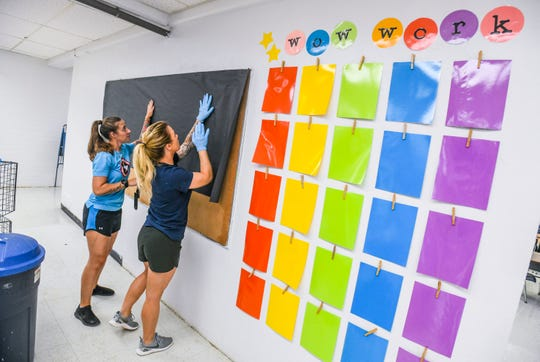 Service members Melissa Miller, front, and Sarah Johnson, with Andersen Air Force Base 36th Security Forces, cover a bulletin board with black construction paper as the duo and other volunteers prepare Juan M. Guerrero Elementary School for the start of classes. Student orientation is scheduled to be held on Aug. 9 and the start of classes is slated for Aug. 13, said Frances Cepeda, school administrative assistant.
