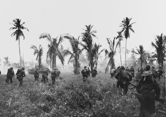 Marines advancing on Guam, in company with an M-4 Sherman tank, July-August 1944.