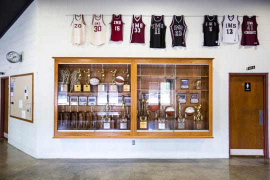 Basketball jerseys hang above a trophy case, Friday, Aug. 2, 2019, at Hillcrest Academy in Kalona, Iowa. Hillcrest was formerly known as the Iowa Mennonite School.