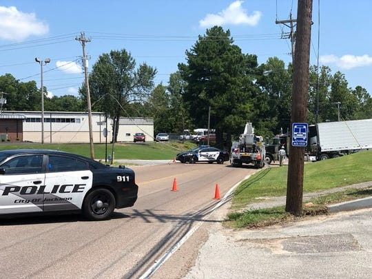 Jackson Police vehicles block the roadway near the intersection of Whitehall Street and Lifsey Drive in Jackson, Tenn., where a tractor trailer downed a line on Aug. 2.
