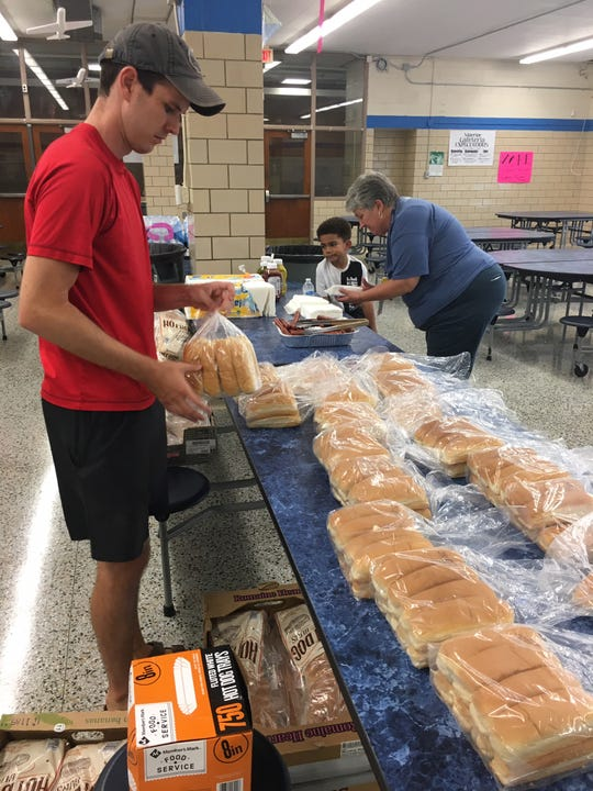The Rev. Wesley Mills of Fellowship North Knoxville unwraps some hot dog buns. Sixth grade math teacher Laura Spinelli helps, while her grandson Zaylen Gordon – whose own middle school career is years away – looks on.