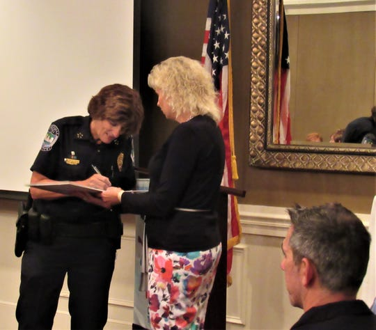 Knoxville Police Chief Eve Thomas signs a children's book presented by Rotary president Staci Wilkerson. Each guest speaker inscribes a book that is then donated to Ball Camp Elementary School.
