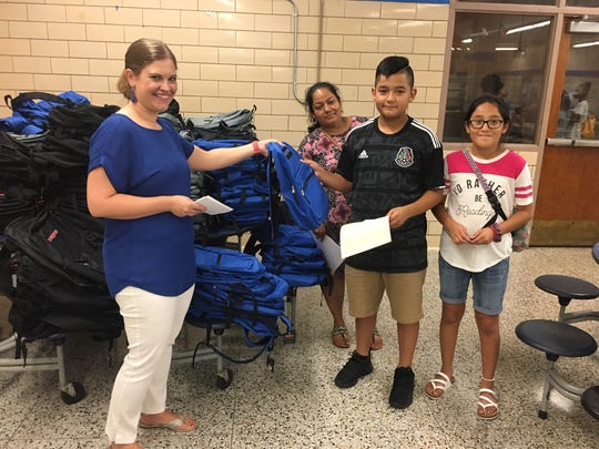 """Liz Thacker, Community Schools Partnership coordinator, is happy to hand over brand new backpacks filled with school supplies to the kids who have completed the """"dash."""" """"Fellowship North Knoxville donates all of this,"""" she said. The proud recipient is Jesus Castaneda, shown with mom Margarita Moreno and sister Saray Castaneda. August 1, 2019."""