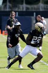 Purdue running back King Doerue (22) avoids Purdue assistant coach Chris Barclay while running a during practice, Friday, Aug. 2, 2019 at Bimel Practice Complex in West Lafayette.
