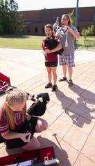Bagpipe instructor Jake Spangler, right, helps Howell High School junior Genna Griffin get set up while sophomore Jorja Vartoogian unpacks her bagpipe Thursday, Aug. 1, 2019.