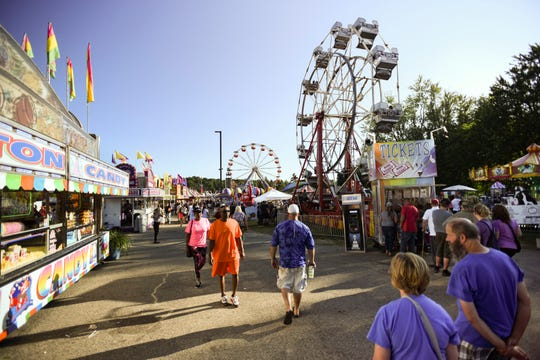 People walk the midway Thursday, Aug. 1, 2019, at the 165th Ingham County Fair in Mason. Ingham, Eaton and Clinton county fair boards are wrestling with how they will ensure safety at their fairs this summer during the COVID-19 pandemic.