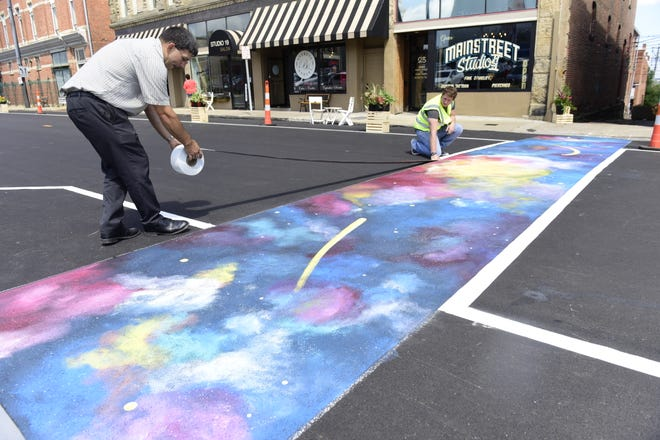 David Gentile, left, and Nick Leturgey, both of the Richland County Regional Planning Commission, apply traffic tape to the borders of a temporary crosswalk across East Fourth Street in the block between Main and Diamond streets.