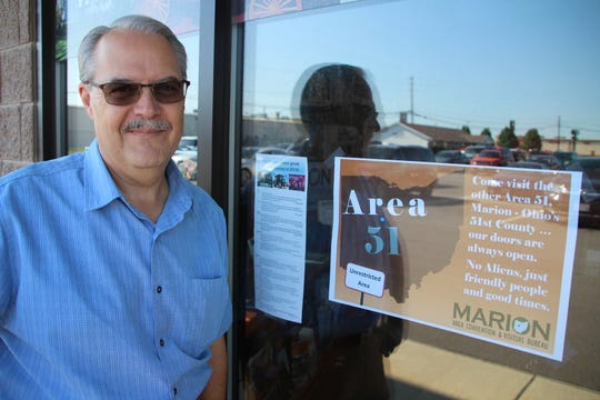 """Marion Holbrook, executive director of the Marion Area Convention and Visitors Bureau, displays one of the Area 51 flyers the CVB is using in its current promotional campaign. The campaign grew out of the recent """"Storm Area 51"""" craze on social media."""