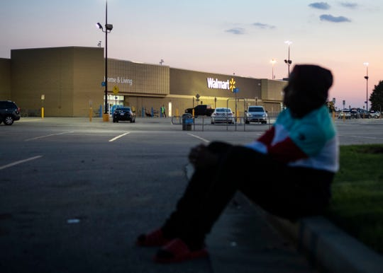 Julian sits on the curb outside of a  Southaven Walmart parking lot after two store employees were killed Thursday, August 1, 2019.