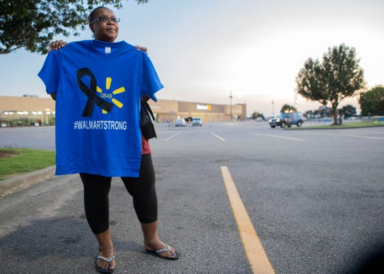 """Beverly Jones, Walmart money center associate, holds a """"Walmart Strong"""" t-shirt  in the Southaven store parking lot Thursday, August 1, 2019 after two store employees were killed earlier in the week."""