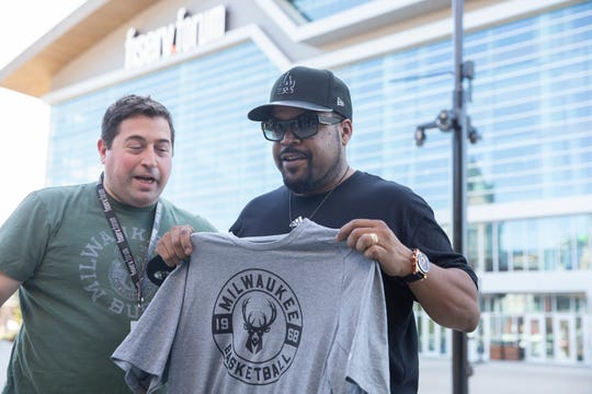 Rapper and Big 3 founder Ice Cube receives a Milwaukee Bucks t-shirt from the Bucks president Peter Feigin.