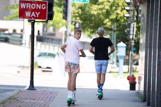 Two people use Lime scooters on the sidewalk in the 300 block of West State Street in Milwaukee on Aug. 2.