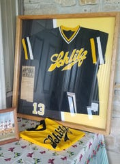 A display shows the jerseys worn by the Milwaukee Schlitz professional men's softball team.
