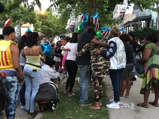 Friends and family gather to remember Lequon McCoy at a vigil Thursday night near North 12th and West Locust streets. McCoy died when a driver being chased by police crashed into his car at that intersection, police said.