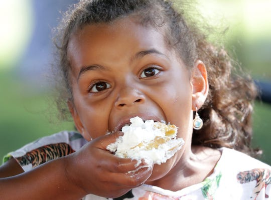 Jaylyn Estinable, 6, of West Allis eats a cream puff Thursday, Aug. 1, 2019, at the Wisconsin State Fair.