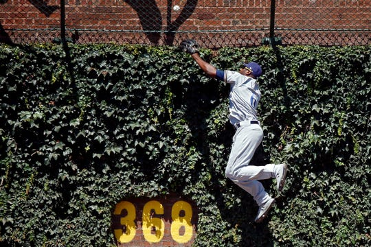 Brewers centerfielder Lorenzo Cain makes a leaping attempt on a ball hit by the Cubs' Jason Heyward that lands in the outfield basket at Wrigley Field for a home run in the bottom of the first inning.