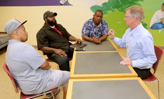 Bill Harrigan (right) is a pioneer in workplace training in Milwaukee. He's shown in August talking with (from left) Taran James, Elijah Tucker-Carter and Johnnie Rose. Harrigan's company is called Harrigan Solutions. Most of his hires are ex-offenders coming out of prison.