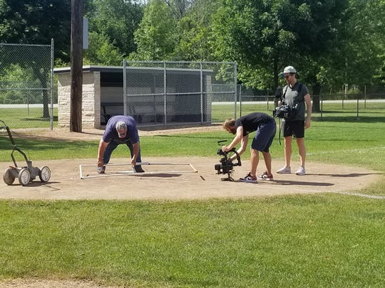 Parks employee Ron Dutcher (left) works on the batters box at Joecks Field in Lannon as an ESPN camera crew captures footage for an upcoming special on the first game ever broadcast on the network in 1979.