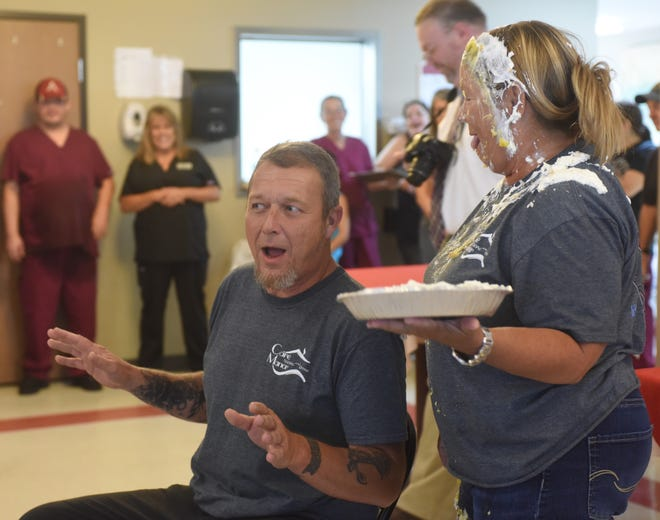 David Short, assistant director of nursing for Care Manor, prepares to receive a pie in the face from nurse practitioner Deb Wilhite on Friday afternoon at Care Manor. Wilhite, who had already received one pie to the face minutes earlier as part of a fundraiser, bid $142 for the opportunity to smash a cream pie in the face of a Care Manor employee of her choosing. Care Manor employees raised more than $1,500 for weekend supervisor Julie Desparrois, who is currently undergoing chemotherapy after being diagnosed with cancer. Wilhite narrowly beat out Short in voting for the honor of taking a pie to the face.