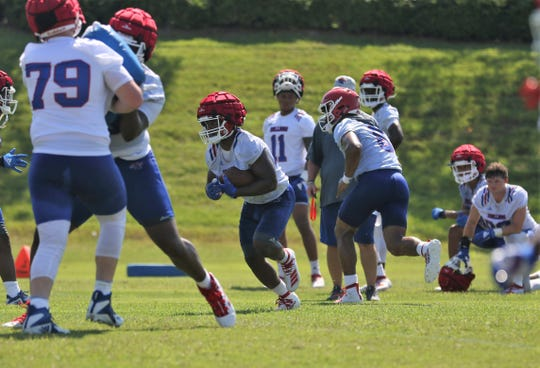 Louisiana Tech redshirt junior running back Israel Tucker (22) runs the ball during the team's first practice of fall camp Friday, Aug. 2, 2019.