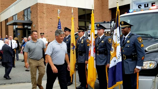 The Morris County Sheriff's Office Honor Guard standing as Detective Captain Bruce Dunn, left, and Chief Edward Crooker pass by on their retirement walkout.
