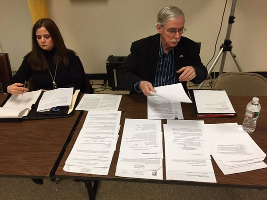 Roxbury petitioner Craig Heard reviews resumes of applicants for a commission being formed to study a possible consolidation of Roxbury and Mount Arlington during a 2015 meeting in Roxbury.