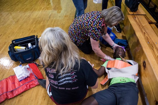 Teachers and faculty respond to Caden Walker, 14, a student actor, during a disaster drill at Prattville Junior High School in Prattville, Ala., on Friday, Aug. 2, 2019. The school and first-responders staged the drill to practice what would happen in a real life scenario. Drama students and their teachers created realistic injuries and acted as victims of tornado damage.