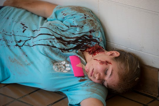 A student actor plays dead during a disaster drill at Prattville Junior High School in Prattville, Ala., on Friday, Aug. 2, 2019. The school and first-responders staged the drill to practice what would happen in a real life scenario. Drama students and their teachers created realistic injuries and acted as victims of tornado damage.