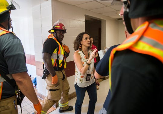Principal Janice  Stockman helps emergency crews during a disaster drill at Prattville Junior High School in Prattville, Ala., on Friday, Aug. 2, 2019. The school and first-responders staged the drill to practice what would happen in a real life scenario. Drama students and their teachers created realistic injuries and acted as victims of tornado damage.