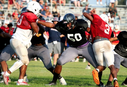 Cane Ridge's Michael Reese holds 2 Oakland players back on the line as the two teams scrimmage at Cane Ridge on Thursday August 1, 2019.