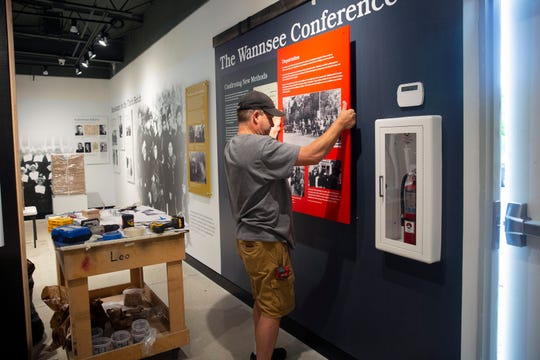 Bryan Connell, a supervisor at Capitol Museum Services works on mounting a display, Friday, Aug. 2, 2019, at the Holocaust Museum & Cohen Education Center of Southwest Florida in North Naples.