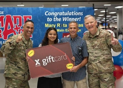 Mary Kostas (center) celebrates her win with Air Force Chief Master Sgt. Luis Reyes, Exchange senior enlisted advisor, and Col. Robert Sylvester, 56th Mission Support Group commander, on July 25.