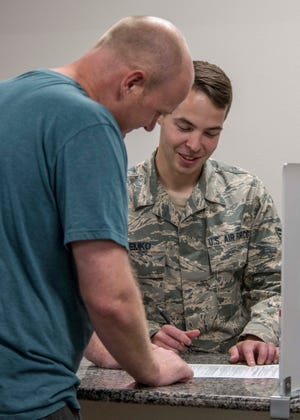 Senior Airman John Demko, 49th Comptroller Squadron financial operations technician, explains the spouse licensure reimbursement program to a customer, July 30, 2019, at the finance office on Holloman Air Force Base, N.M. On May 13, 2019, the Air Force implemented a licensure reimbursement program, not to exceed $500, for dependent spouses who require a relicensure or recertification during a permanent change of station or assignment across state lines.