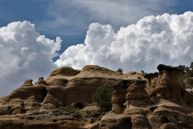 Afternoon clouds build in the sky above a sandstone formation at the Glade Run Recreation Area north of Farmington on Aug. 2.