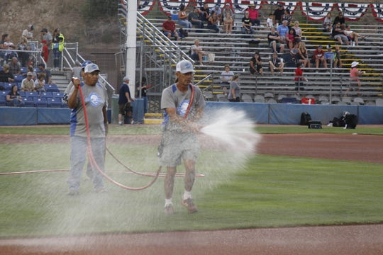 Doug Abe waters the infield in between games at the Connie Mack World Series.